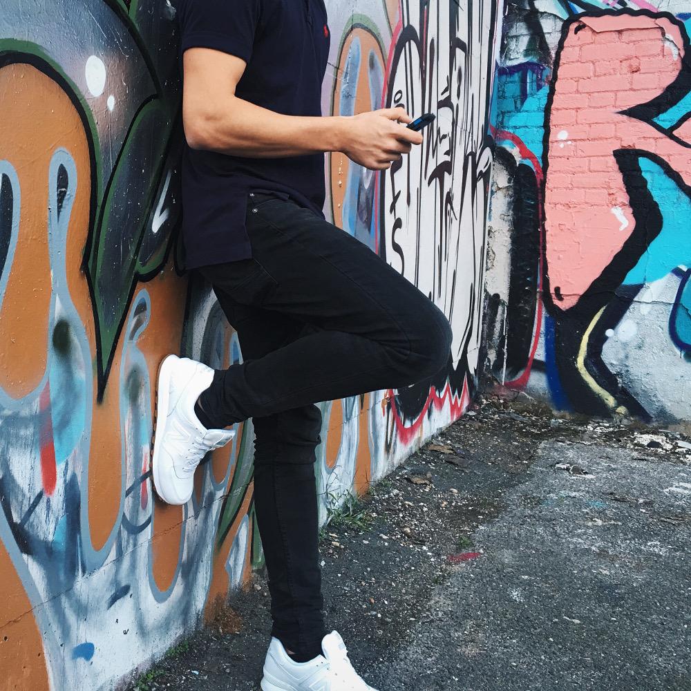 homme adossé à un mur taggé portant un t shirt noir un jean noir et des baskets blanches