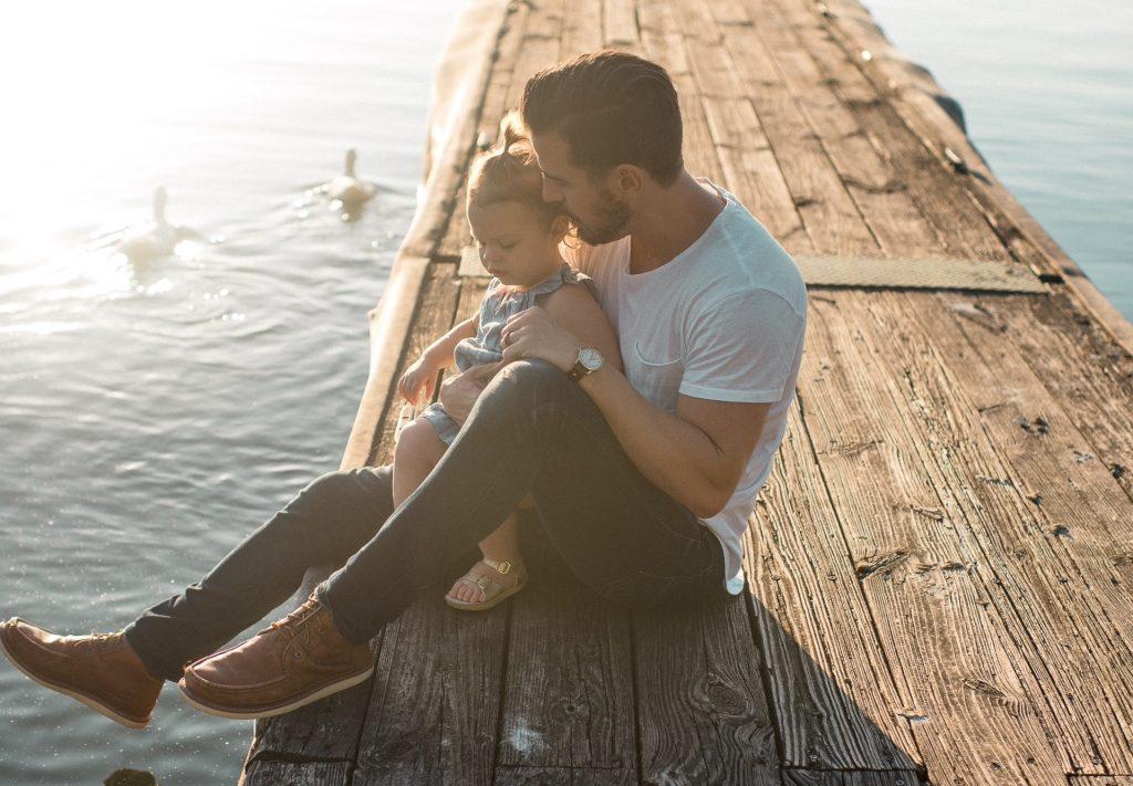 papa portant un t shirt blanc un jean et des mocassins avec sa fille entre les jambes sur un ponton au bord de l'eau